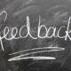 Mit Kreide auf schwarzer Tafel geschrieben steht: feedback
