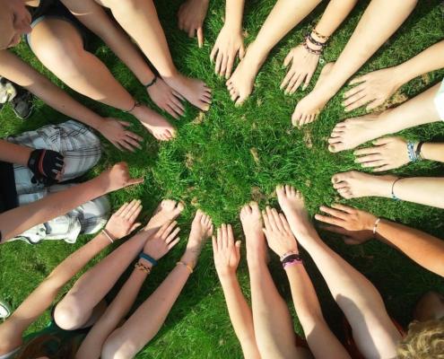 Nackte Hände und Füße sind im Kreis angeordnet, der Hintergrund ist eine Rasenfläche