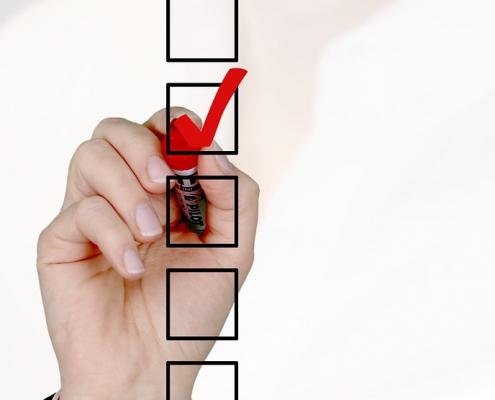 Hand setzt mit rotem Textmarker ein Häkchen in eine von fünf übereinander angeeordneten Kästchen