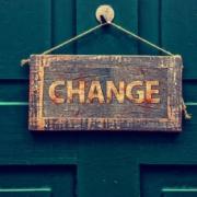 """Detailaufnahme einer grünen Tür vor der ein Schild mit der Aufschrift """"Change"""" hängt"""