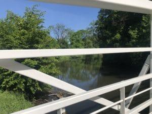 Detail eines weißen Brückengeländers, im Hintergrund ein Fluß mit bewaldetem Ufer